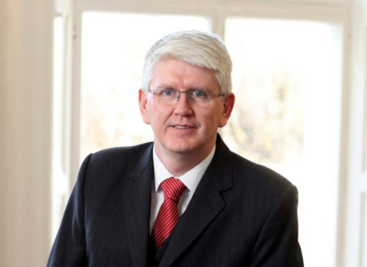 Headshot of IUA director general Jim Miley wearing black suit and red tie with a window in the background.