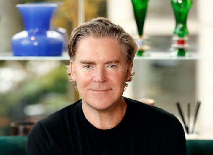 Headshot of Daniel Kiely smiling in front of a blurred background.