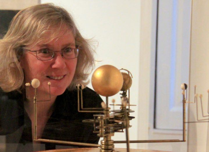Photo of Mary Mulvihill looking at a golden model of the solar system and smiling.