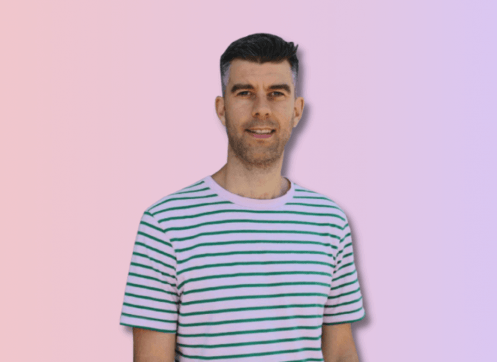 Publift founder Colm Dolan in a blue and white striped shirt against a soft pink background.