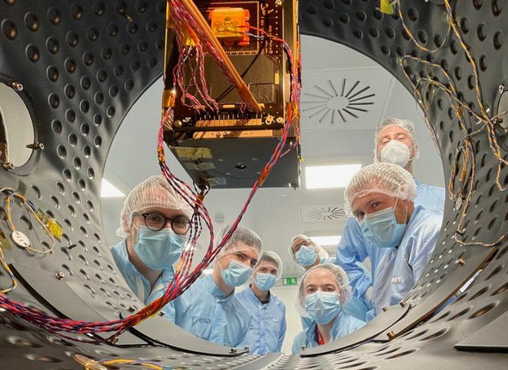 A group of people in protective gear look into a container that is housing the small cube-shaped satellite.