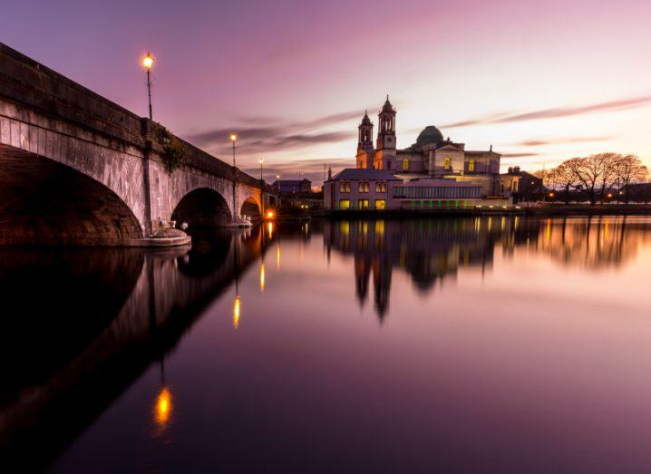 Photo of Athlone bridge over the Shannon River at dusk with town in background.