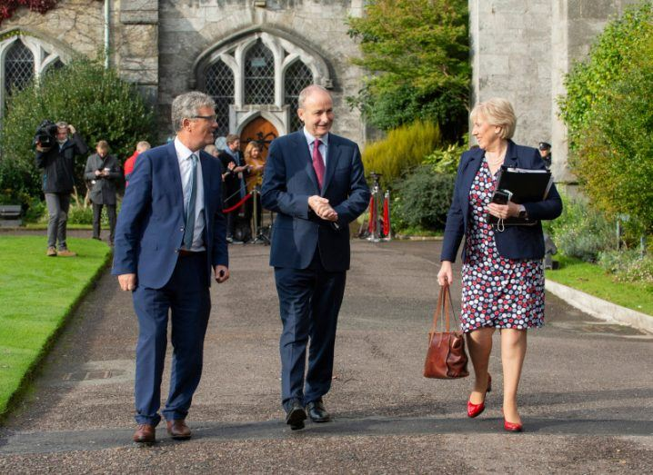 John O'Halloran, Micheál Martin and Heather Humphreys walking in the grounds of UCC and talking to each other. Trees and buildings are in the background.
