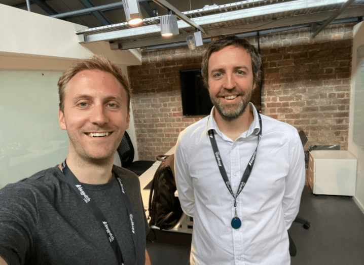 Two men wearing Dogpatch Labs lanyards stand in a small office space with an exposed brick wall behind them.